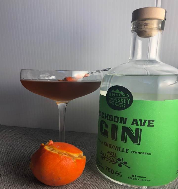 Photo of the Martinez Cocktail in a coupe glass with a satsuma in front and a bottle of Jackson Avenue gin to the right.