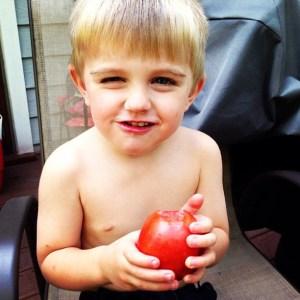 Brogan eating a tomato
