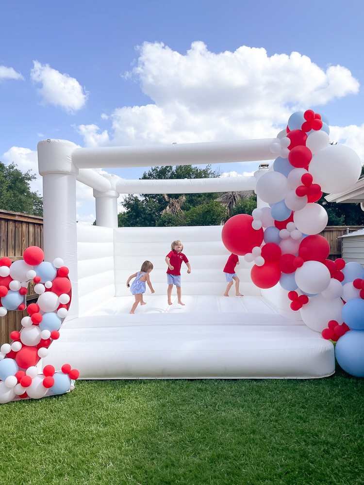 children jumping in white bounce house