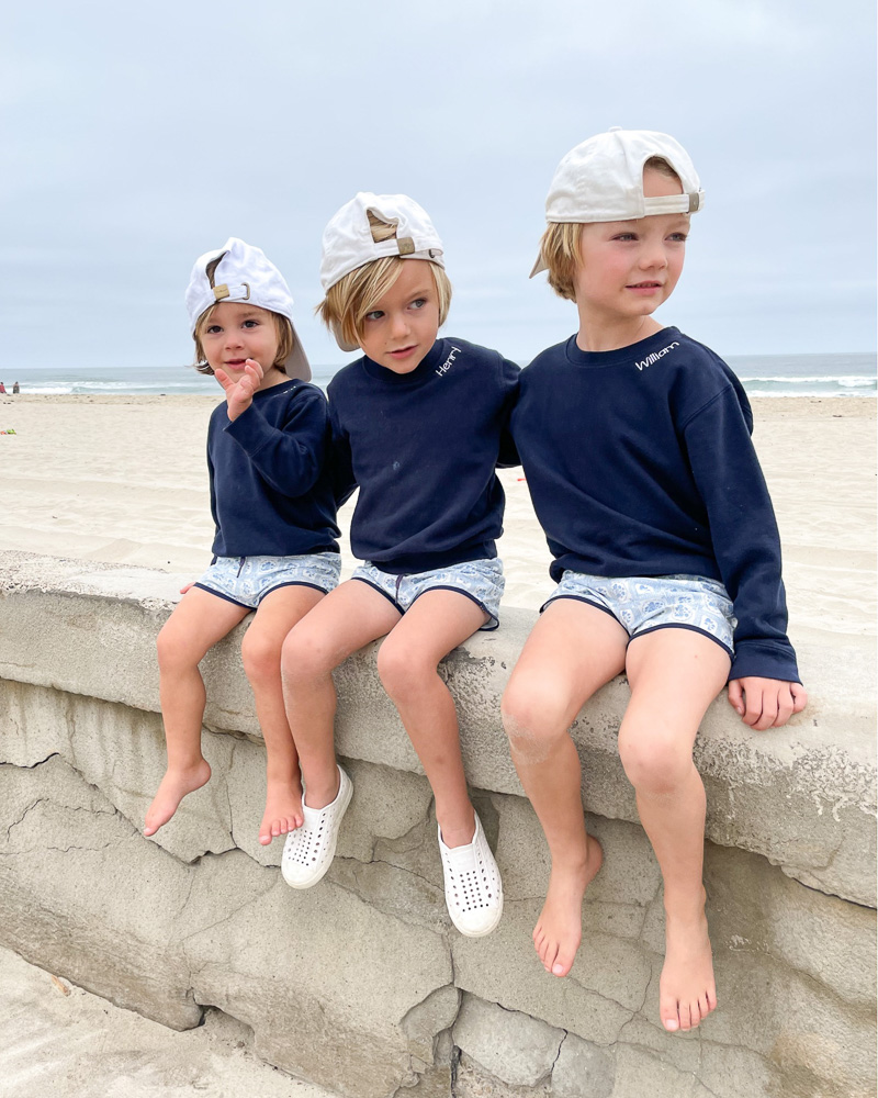 three little boys sitting on sea wall in matching outfits
