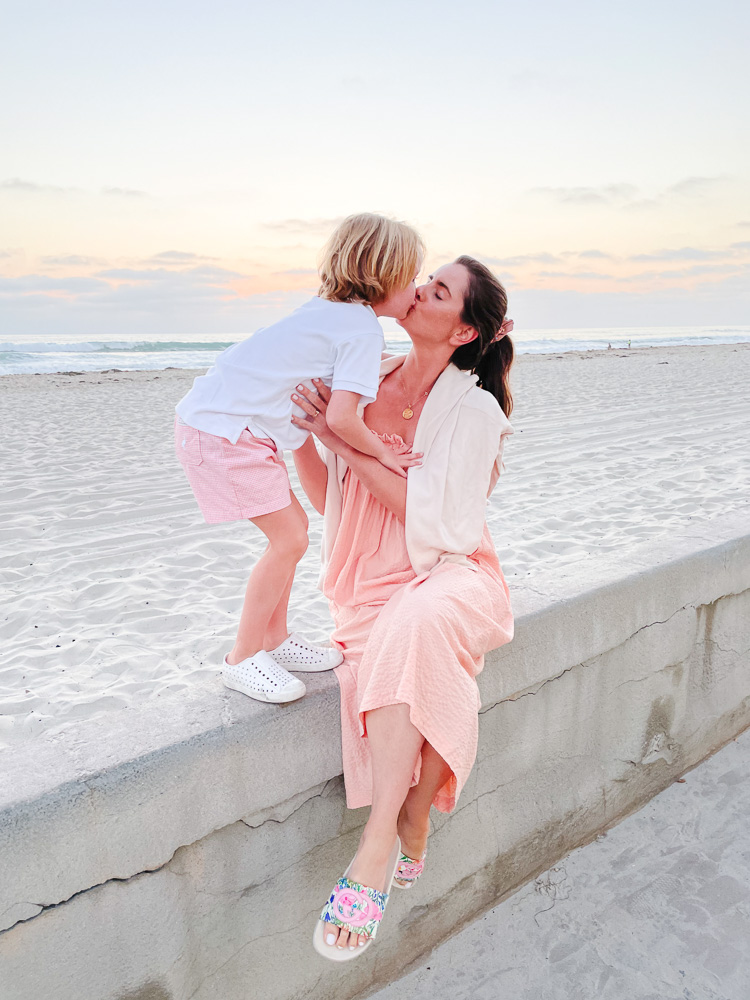 mom and son kissing beach side