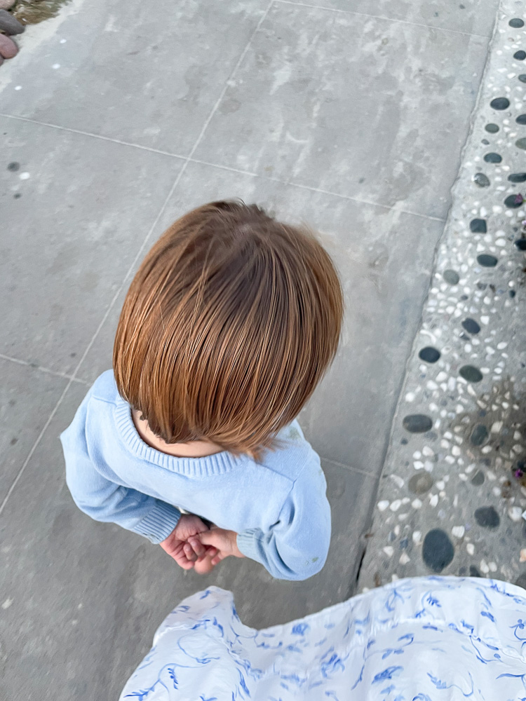 toddler walking with hands behind back
