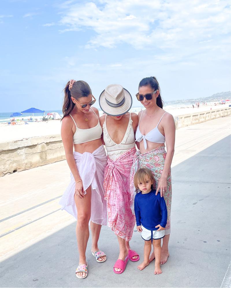 three women with toddler on beach boardwalk