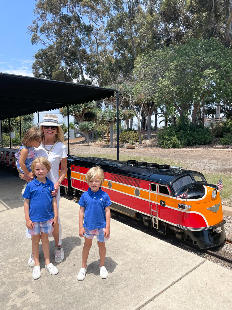 woman with three little boys at toy train ride