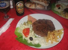 A real Pljeskavica (meat mixed with tiny pieces of onion) with pita bread, some potatoes, tasty sauces, french fries, salad, cabbage, onion and a tomato and olive. Oh, there's also Birra Peja (a beer from Peja/Peč, Kosovo) - the best beer in Kosovo... Ooops, it's the only one actually. :)