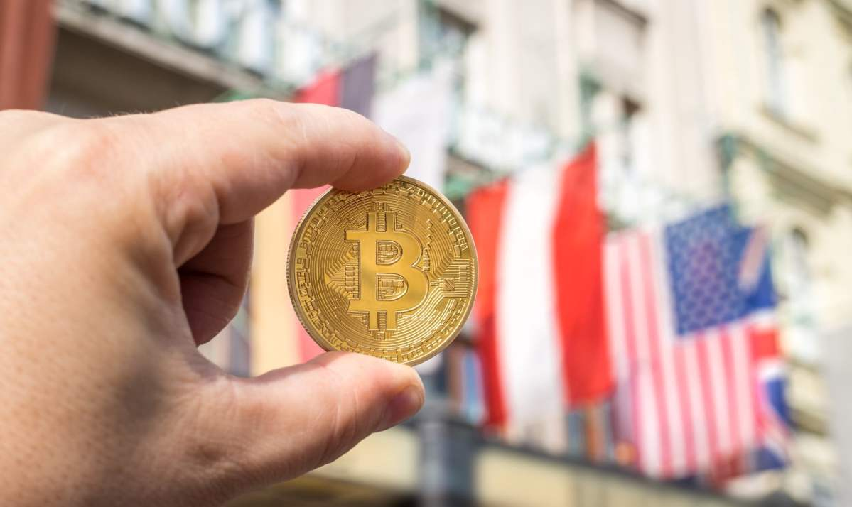 Bitcoin Münze vor Österreich Flagge