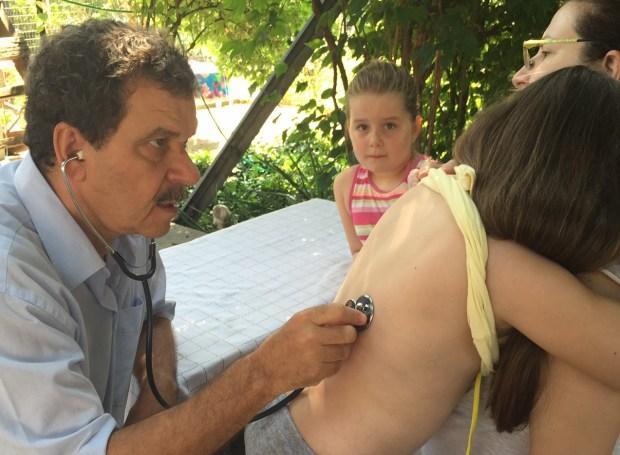 Prof. Giannis behandelt umsonst ein Kind in Griechenland. Das Kind hatte Husten, und die Mutter machte sich Sorgen. Giannis hat festgestellt, dass es lediglich eine abklingende Bronchitis ist. Der nächste Arz wäre 30 Kilometer weit weg gewese ...