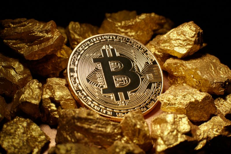 Berlin, Germany - July16, 2017: Golden Bitcoin Coin and mound of gold. Bitcoin cryptocurrency. Business concept.
