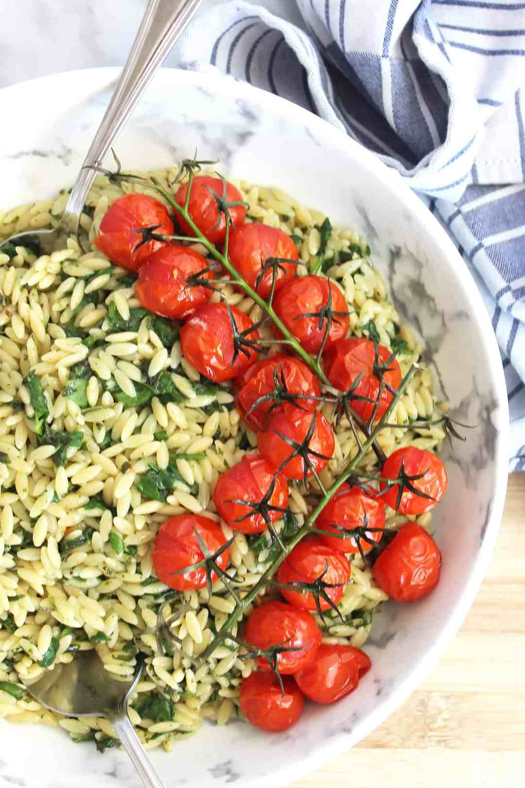 Roasted tomatoes on a bed of spinach orzo salad