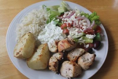 Chicken souvlaki served with Greek roast potatoes, rice pilaf, romaine Greek salad with feta cheese, and tzatziki sauce.
