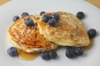 Pancakes with blueberries and chocolate chips cooked into the batter, served with blueberries and drizzled with a generous amount of maple syrup.