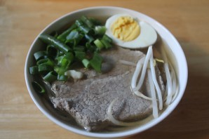 Ramen soup topped with sliced beef, hard boiled egg, scallions and bean sprouts.