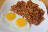 Crispy shredded potatoes served with fried eggs sunny-side-up.