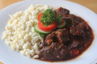 Stewed beef served with nokedli and vegetables.