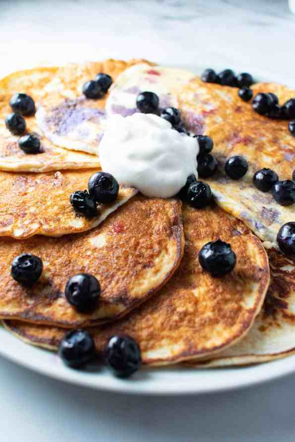 coconut pancakes on a white plate with blueberries