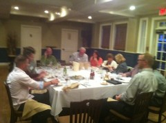 Members sit around a large table facing each other and engage interesting conversation