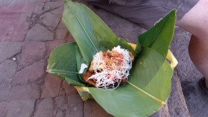 Enchiladas with slaw and chilli sauce served in banana leaf