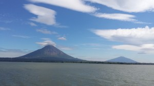 Two volcanoes seen across a lake. The one to the left taller than that to the right.