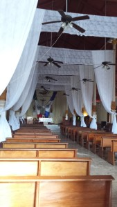 interior of church with wooden pews and white drapes