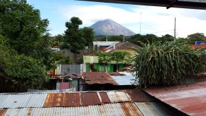 a view from a hotel balcony in Moyogalpa, Ometepe.  Tin roofs of buildings in the foreground lead to the majestic Volcan Concepcion with a cap of cloud on its summit in an otherwise blue sky
