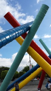 sculpture made up of red, yellow and blue barrels joined together and set at angles against each other