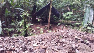basic shelter of upright tree pole and black plastic tarpaulin set beside the river in the jungle