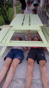 girls lying underneath tables painting the underside of them