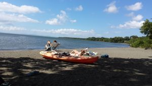 orange kayak on beach and girls sitting on sun loungers, blue water of lake and blue sky.