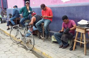 street in Rivas with men cleaning shoes sitting on the side of the road.  One man having his shoes cleaned, a bicycle propped against the kerb.