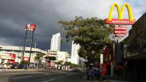 main street in San Jose, Costa Rica.  MacDonalds and KFC signs dominate the skyline