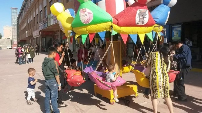 "Contrasting images of Xinjiang: children playing on the carousel against a background of the Hotan market ""home guards"" practicing a drill."