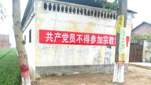 "A banner hanging on the wall, reading ""Communist Party Members Cannot Participate in Religious Activities."""