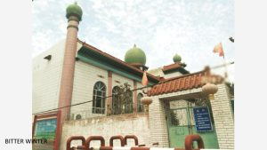 The mosque in Liugong village's No.7 Production Team has been shut down, and the perimeter wall has been covered with barbed wire. Two Chinese flags have been erected, one on each side of the entrance.