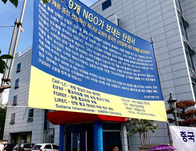 The peaceful answer of the refugees: a banner with the appeal of the nine NGOs