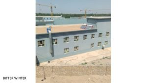 """Unfinished two-story buildings inside the Chengnan """"transformation through education camp."""" Some windows have been closed, and the roof is under construction."""