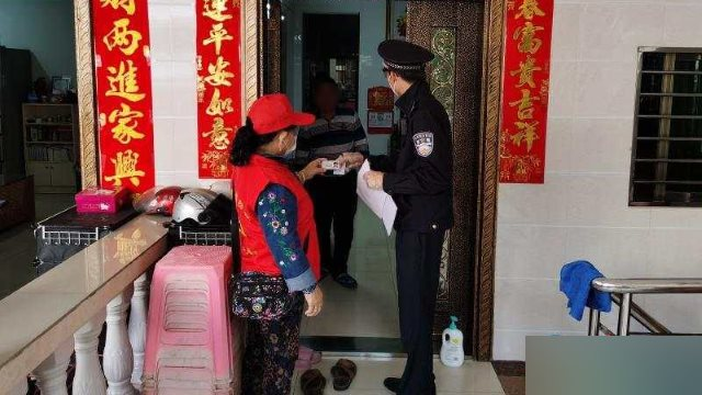 In Sanya city, Hainan Province, a community personnel member, together with a police officer, goes door-to-door to verify residents' ID information.