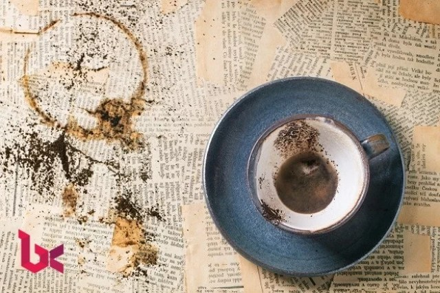 Blue ceramic cup of coffee grounds over old newspaper. Top view.