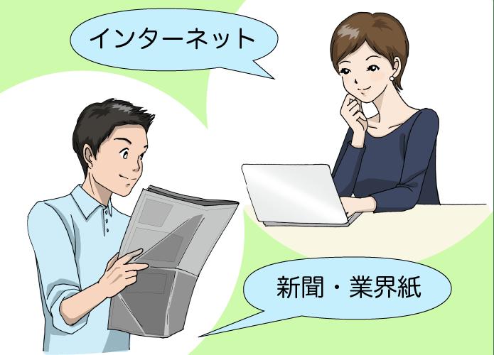 新聞を読む男性とパソコンを使っている女性