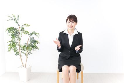 椅子に座って明るく話す女性