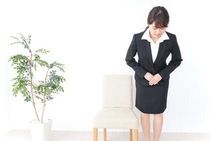 椅子の横でお辞儀をする女性(正面)