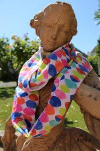 le snood multicolore porté par un mannequin original : la statut de pierre du jardin !
