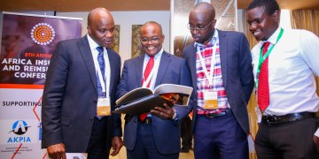 Liberty Life Managing Director, Abel Munda (second left), interacts with, Turnkey Africa Limited- CEO, Kizito Makatiani (left) and Forensics PWC- Senior Manager, John Kamau (second right) and CWD Limited- Managing Director, Edwin Magalasie peruse through a document during the 08th Annual Africa Insurance & Reinsurance Conference held in Nairobi.