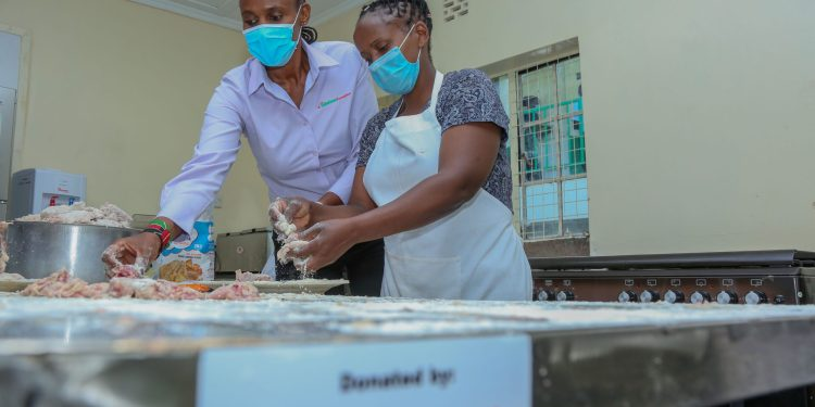 Catherine Muthoni a student at Waithaka Technical and Vocational Centre in the catering department taking Eunice Kibathi, Safaricom Foundation Programmes manager, through the process of marinating chicken wings during the refurbishing of the institution at a cost of KES 28 million - Bizna Kenya