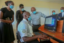 Joseph Ogutu, Safaricom Foundation Chairman, Acting County Chief Education –Nairobi, Ruth Owuor (center) together with the ICT Teacher Evelyn Wambui (left) being taken through the new learning computer programme by Aquinas Rabin a student at Waithaka Technical ICT lab - BIzna Kenya