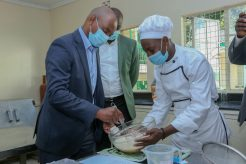 Steve Chege, Safaricom Foundation Trustee, (left), being taken through the process of baking a cake by Joseph Hunja a student at the Waithaka Technical Centre taking the Food and Beverage course. The center in Waithaka will see 200 students supported over the next 2 years - Bizna Kenya