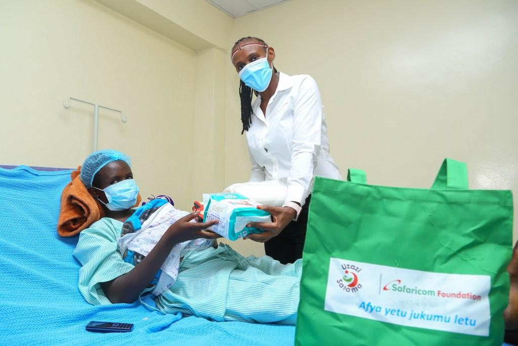 Safaricom Foundation's Eunice Kibathi (right) hands over a Mama Pack to Miriam Cheptoo during the handover of a HDU AND NBU in Baringo County Referral Hospital - Bizna Kenya
