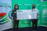 Safaricom plc Isaac Gathogu (L) hand over a dummy cheque of two million shillings to Maxine Wahome (Center) and her co-driver Linet Ayuko (L) during Safaricom cheque handover at Safaricom headquarter - Bizna Kenya