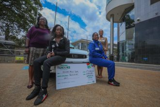 Rally Driver Maxine Wahome (R) and her co-driver Linet Ayuko (L) pose for a picture after Safaricom's sponsorship cheque handover - Bizna Kenya