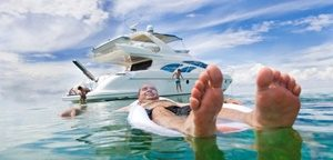 Man floating on inflatable bed with yacht and people in background