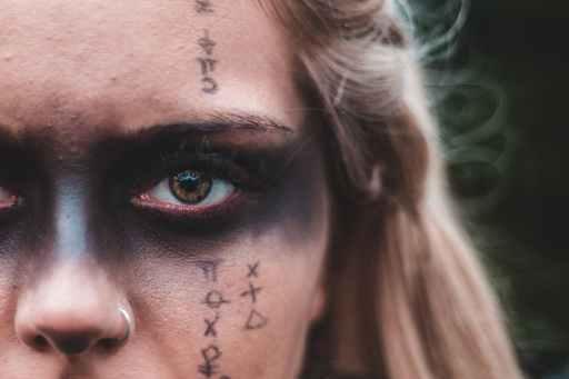 Une femme portant un maquillage noir avec es runes inspiré de la mythologie nordique